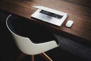 Tisch mit Macbook und Sessel