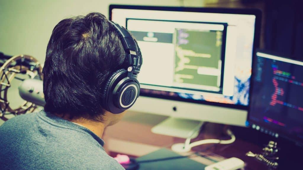 Mann mit Kopfhörern vor Bildschirmen