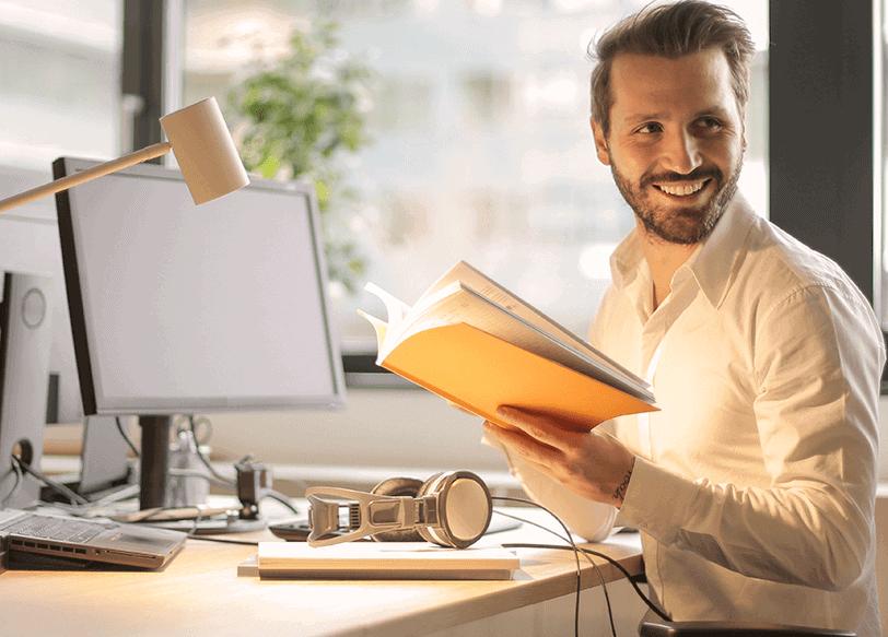 Mann mit Buch in der Hand im Büro
