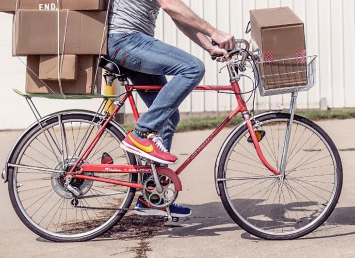 Mann auf Rad mit vielen Paketen