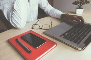 Laptop und Notitzbuch auf einem Tisch-buchhaltungssoftware online