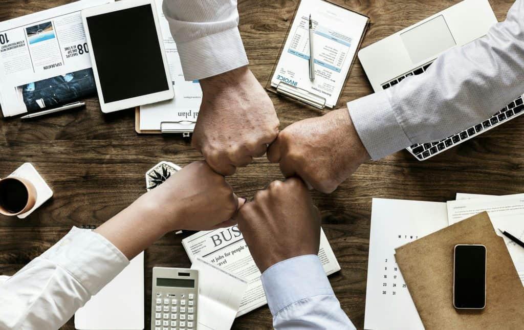 Hände die sich in der Mitte treffen über Arbeitsmaterialien
