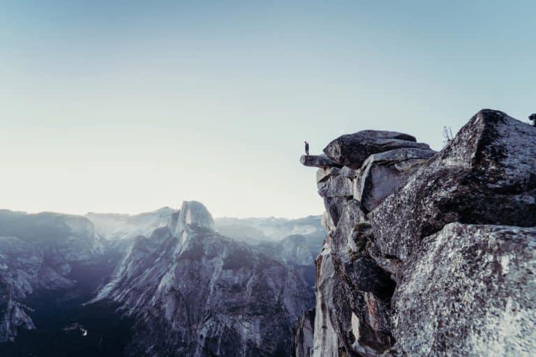 Mensch steht vor einer Klippe
