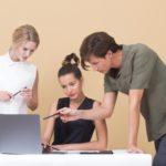 Drei Menschen stehen vor einem Laptop und schauen auf den Bildschirm