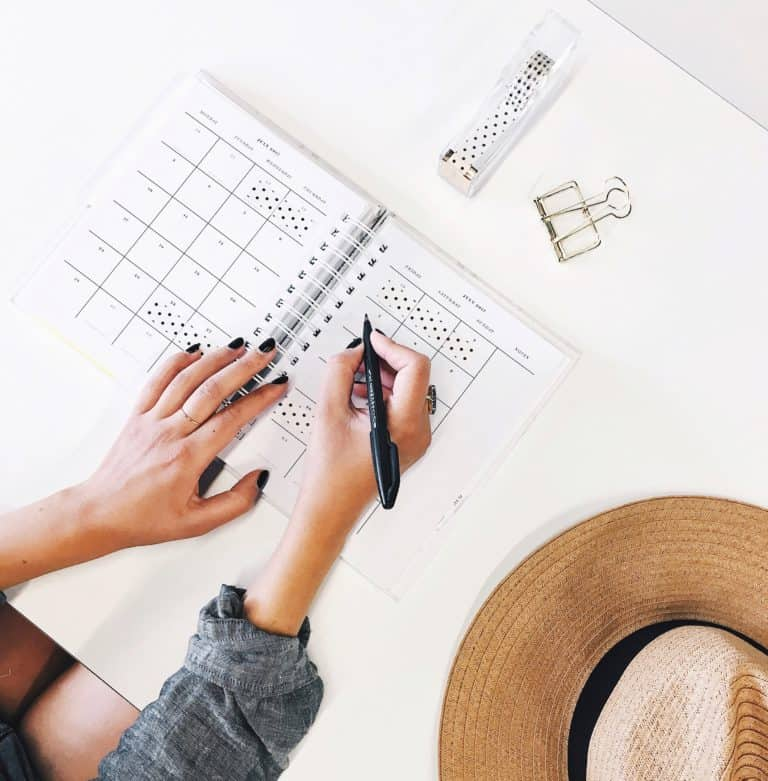 Frau schreibt in einen Kalender für den Monatsabschluss